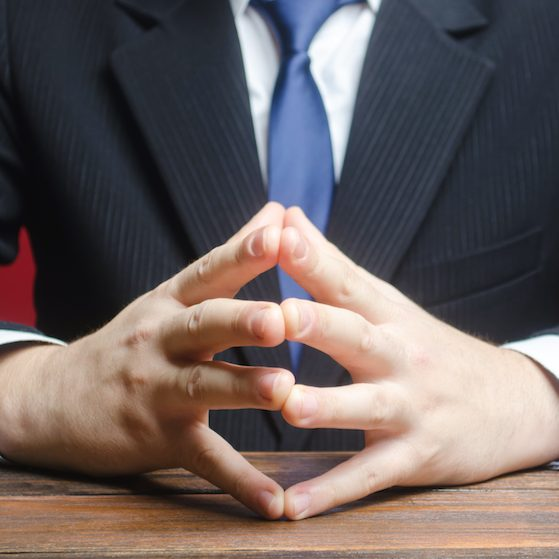 A man sits with his hands in the lock. Conflict resolution, search for a compromise. Pondering a problem, finding consensus. Businessman in thought. Composure and professionalism. Make right decision